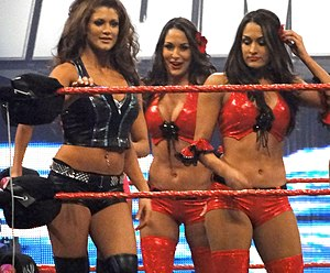 3 dark-haired women in a wrestling ring with red ropes. The one on the left is wearing a dark green crop top and shorts, and is holding onto to the top rope with her right hand. The other two are identical twins, and are both wearing red crop tops and shorts.