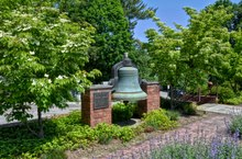 A brass bell displayed beside a sidewalk and trees
