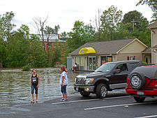 Two cars parked near the edge of water in a parking lot. A Subway restaurant can be seen in the background, and two young people are at the edge of the water.