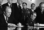 Two men in suits are seated, each signing a document in front of them. Six men, one in a military uniform, stand behind them.