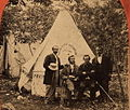 Four men in front of a tent with a sign for the Boston Daily Advertiser, cropped.jpg