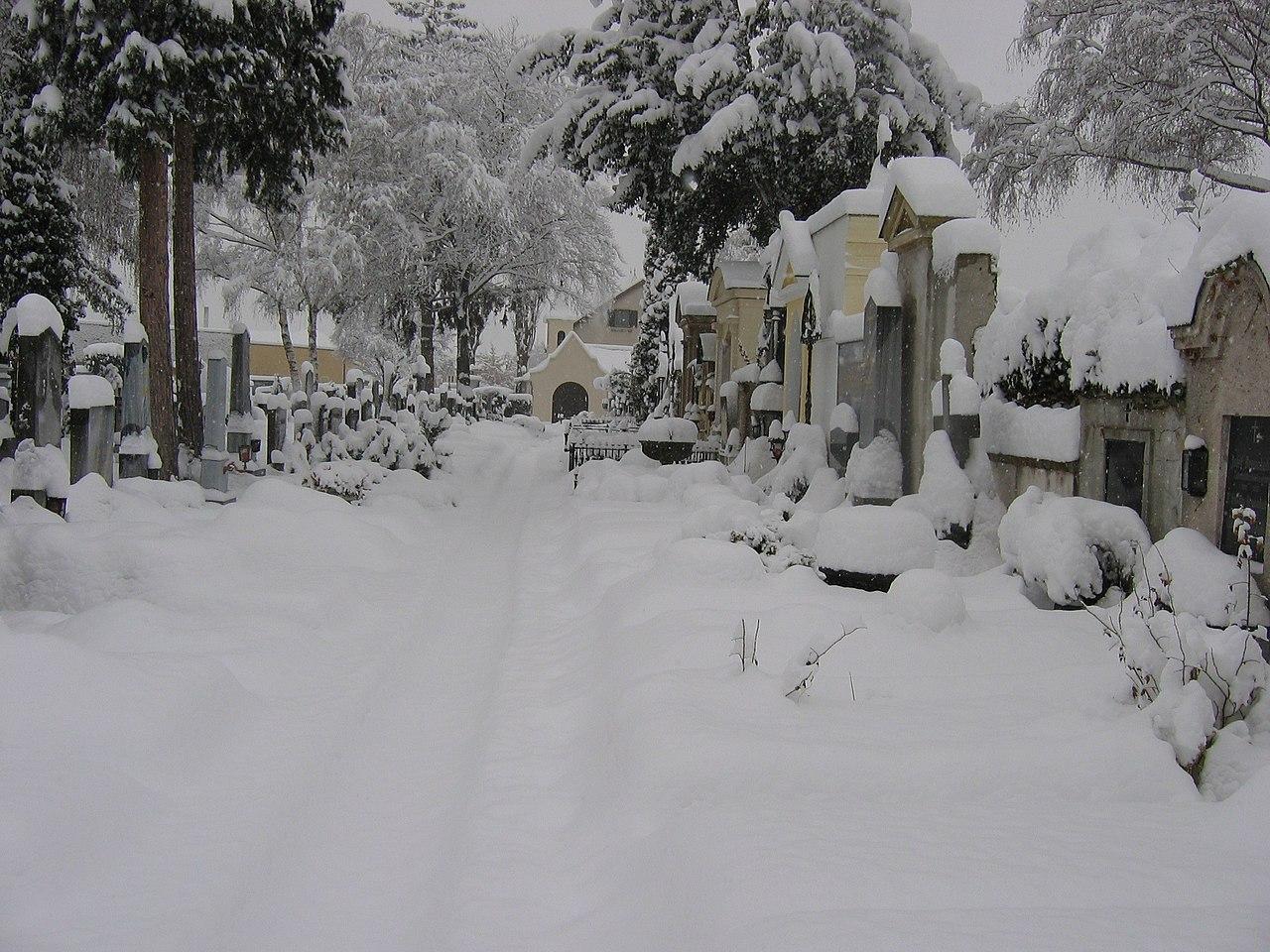 Fotografie eines schneebedeckten Friedhofs im Winter.