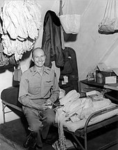 Halvorsen sitting on cot in barracks surrounded by handkerchiefs to be made into parachutes