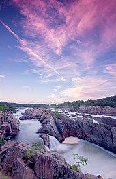 Rápidos en un río ancho y rocoso bajo un cielo azul con nubes de color púrpura por la puesta de sol.