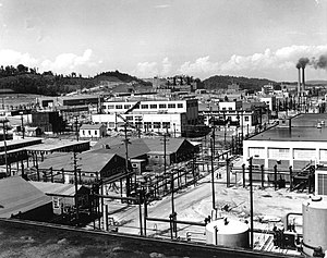 An array of industrial buildings with lots of power poles and wires, with a pair of smokestacks in the background