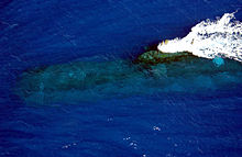 Aerial view of a submarine just below the water's surface. The body of the submarine is distorted, and only the wake from three upright projections can be seen clearly.
