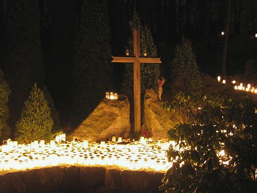 Hundreds of candles and a Christian Cross at a cemetery on Christmas eve