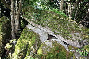 moss covered upright stones support a massive leaning stone roof slab