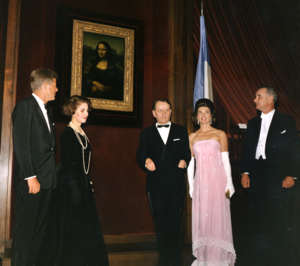 Three men and two women stand near the Mona Lisa. All are dressed formally, one woman in a spectacular pink gown.