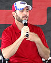 A man in his mid thirties speaking into a microphone. He is wearing a red and white baseball cap and a red t-shirt.