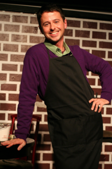 A grinning man in front of a faux-brick wall wears a purple shirt under a black apron while leaning with his right arm on a low table
