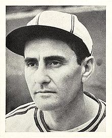 A man in a white baseball jersey and cap with dark stripes looks to the left.