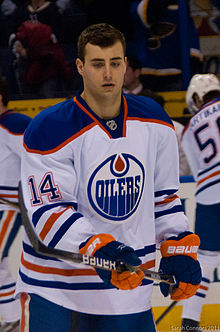 "A Caucasian ice hockey player wearing a white jersey with a blue and orange circular logo with the word ""OILERS""."