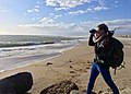 Karen Sinclair, a fish and wildlife biologist with the U.S. Fish and Wildlife Service in Ventura braces against the wind while looking for brown pelicans during the biannual brown pelican survey held along the West Coast. (34375760720).jpg