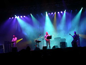 King Crimson - King Crimson performing in 2003 Left to right: Trey Gunn, Adrian Belew, and Robert Fripp (Pat Mastelotto is hidden)