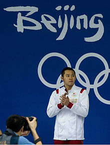 "Asian man with short black hair, in white tracksuit stands on the podium waiting to receive his medal. Behind him is a blue wall with the words ""Beijing"" and ""2008"" in white."