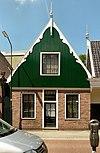 foto van Grotendeels houten huis, waarvan het zadeldak wordt afgesloten door een houten topgevel met uitgeschulpte windveren. Bakstenen pui