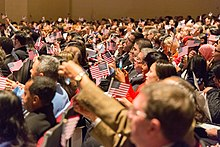 Dozens of adults sit in auditorium rows, many waving small American flags