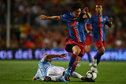 A man named Lionel Messi, wearing FC Barcelona's jersey, dribbling past a player.