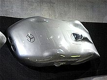 A streamlined silver car with a small transparent canopy on the top for the driver to see through. The Mercedes-Benz logo is displayed prominently on the front.