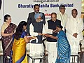 Manmohan Singh presents the new account kit to the first account holder, at the inauguration of the first branch of Bharatiya Mahila Bank Limited, in Mumbai. The Governor of Maharashtra, Shri K. Sankaranarayanan (1).jpg