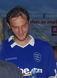A man in his 20s, wearing a blue shirt with white trim.