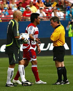 Referee - A referee (right) issues a yellow card to a player during a game of association football.