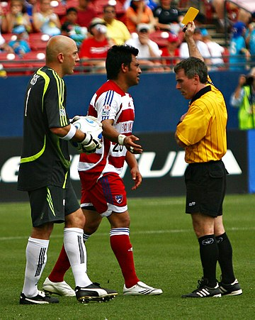 A player is cautioned and shown a yellow card. Matt Reis Carlos Ruiz yellow card.jpg
