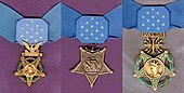 "Three medals, side by side, consisting of an inverted 5-pointed star hanging from a light blue ribbon with 13 white stars in the center. Left medal has a laurel wreath around the star and an eagle emblem above the star; central medal has an anchor emblem attaching the medal to the ribbon; rightmost medal has a laurel wreath around the star and an emblem with wings, lightning bolts and the word ""VALOR"" connecting the medal to the ribbon."