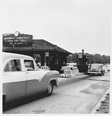 A toll booth with several cars at it on the Merritt Parkway