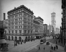 Высокое внушительное каменное здание на почти пустой городской улице, мимо проезжает трамвай.  Башня на заднем плане - единственное другое высотное здание.