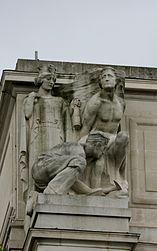 Stone statue of two figures: a man standing on the left with a heavy load on his shoulders a woman standing on the right in a helmet holding a ship's mast