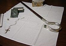 Een staf, borstkruis, bisschoppelijke ring en jade doos bovenop een wit doek dat een donkerbruine houten tafel bedekt