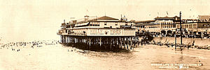 "A black-and-white postcard shows a photograph, taken from a location on the water, of a large building sitting on pier by the beach. The beach is fronted by a seawall and a crowded waterfront beyond. The caption on the postcard says ""Where life is worth living at Galveston""."