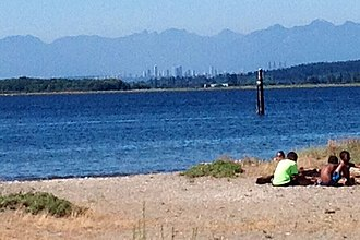 Crescent Beach, Surrey - North-facing view of Mud Bay at high tide from Blackie Spit. Skyscrapers in Burnaby and the North Shore Mountains visible in distant background