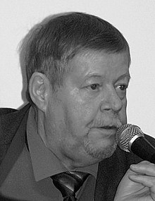 Sepia photo: Face shot of Arto Paasilinna, speaking in a microphone.