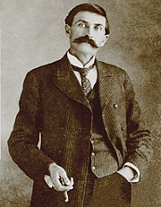 black and white photo of slender man in old-fashioned suit and sporting a large moustache