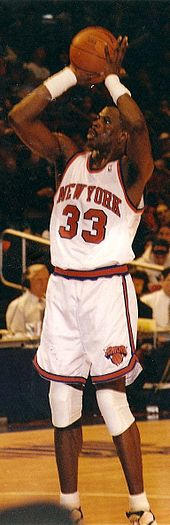 "An African American basketball player attempts a jump shot. He wears a white jersey with an orange ""NEW YORK"" and ""33"", and spectators can be seen in the background."