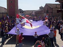 People at a celebration holding a huge purple flag.  Others wave different flags, such as the Cross of Burgundy or the modern flag of Castile and León.