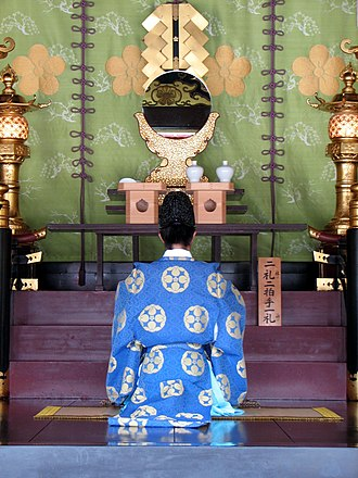 Eastern religions - A Shinto priest kneeling before a shrine.