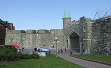 Quebec's restored city wall is gray stone about 20 feet (6.5 meters) high. The St. John's gate has a modern road going through it, and has a copper-roofed turret on the left bastion. A paved path goes through a grassy area below the wall.