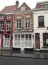 foto van Huis met eenvoudige witte lijstgevel, schilddak en lelie-ankers