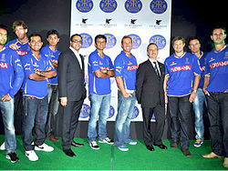 Nine players standing on a green carpet wearing a blue top and blue or black jeans. Along with them are two other men who are wearing black coats and pants.