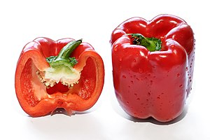 A whole and halved red bell pepper