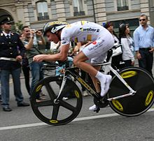 A cyclist wearing a white skinsuit while riding a bike.