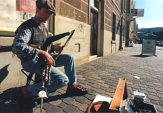 "Richard ""Dicky"" Deegan, piper, busking with his full set in Salamanca Place, Hobart, Tasmania, Australia in 1995 Richard Deegan, piper, Salamanca Place, Hobart, 1995.jpg"