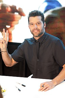 A man wearing a black shirt is showing the two-finger peace sign