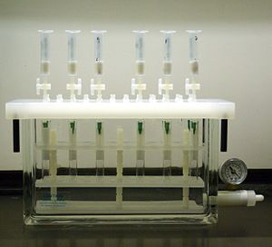 Solid phase extraction - A typical solid phase extraction manifold. The cartridges drip into the chamber below, where tubes collect the effluent. A vacuum port with gauge is used to control the vacuum applied to the chamber.
