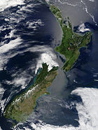 New Zealand from space. The snow-capped Southern Alps dominate the South Island, while the North Island's Northland Peninsula stretches towards the subtropics