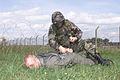 "Senior Airman Daniel Priesman, 52nd Security Forces Squadron, handcuffs downed ""enemy pilot,"" Staff Sgt Eric Doyle, of the 48th Communications Squadron, during a phase II exercise July 24, 2001, Royal Air Force 010724-F-RQ538-009.jpg"